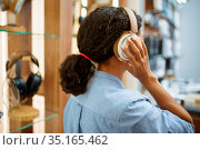 Woman trying on headphones in acoustics store. Стоковое фото, фотограф Tryapitsyn Sergiy / Фотобанк Лори