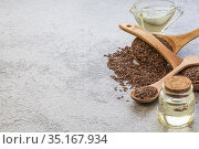 Linseed oil in a glass bottle and flaxseed vegetable source of omega-3, lowers cholesterol, used in food as a dietary salad dressing, in cosmetology, in herbal medicine. Стоковое фото, фотограф Светлана Евграфова / Фотобанк Лори