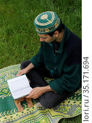 Young man reading the Kuran in a garden in France. Стоковое фото, фотограф Philippe Lissac / Godong / age Fotostock / Фотобанк Лори