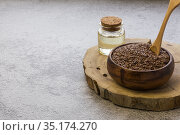 Linseed oil jar wooden bowl with flax seeds on concrete background, dietary cereal ingredient that reduces cholesterol, a source of omega-3, iodine, phosphorus, potassium, magnesium, nickel, vitamin B. Стоковое фото, фотограф Светлана Евграфова / Фотобанк Лори
