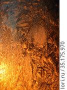Восходящее солнце светит через стекло с морозными узорами. Стоковое фото, фотограф Наталья Горкина / Фотобанк Лори