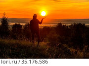 lovely athletic mature woman holding the sun in her palm at sunrise. Стоковое фото, фотограф Акиньшин Владимир / Фотобанк Лори