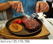 A men in a restaurant eats a Striploin steak served. Стоковое фото, фотограф Мария Сибатрова / Фотобанк Лори