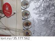 Спутниковые антенны Национальной спутниковой компании Триколор ТВ и МТС установлены на углу дома в провинциальном городе России. Редакционное фото, фотограф Николай Винокуров / Фотобанк Лори