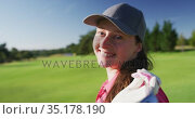 Portrait of female golf player smiling with gold club on her back on golf course. Стоковое видео, агентство Wavebreak Media / Фотобанк Лори