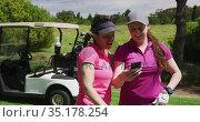 Two caucasian women playing golf using a smartphone. Стоковое видео, агентство Wavebreak Media / Фотобанк Лори
