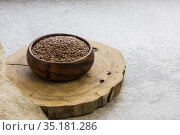 Flax seeds in a wooden bowl on a concrete background, a dietary cereal ingredient for granola that reduces cholesterol, a source of omega-3, vitamins B and C, iodine, phosphorus, potassium, magnesium. Стоковое фото, фотограф Светлана Евграфова / Фотобанк Лори
