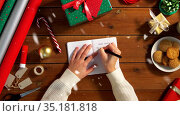 female's hands writing letter to santa in notebook. Стоковое видео, видеограф Syda Productions / Фотобанк Лори