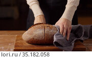 female baker cutting homemade bread at bakery. Стоковое видео, видеограф Syda Productions / Фотобанк Лори