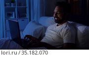 indian man with laptop in bed at home at night. Стоковое видео, видеограф Syda Productions / Фотобанк Лори
