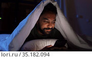 indian man with smartphone in bed at home at night. Стоковое видео, видеограф Syda Productions / Фотобанк Лори