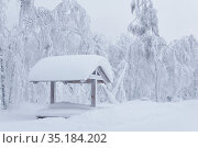 Wooden gazebo with picnic table in a snowdrift after a heavy snowfall in a frosty winter park. Стоковое фото, фотограф Евгений Харитонов / Фотобанк Лори