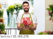smiling male seller with bunch of peony flowers. Стоковое фото, фотограф Syda Productions / Фотобанк Лори