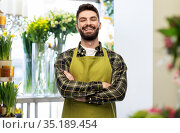 happy young male seller in apron at flower shop. Стоковое фото, фотограф Syda Productions / Фотобанк Лори