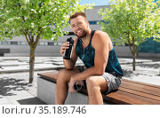 sportsman with earphones and bottle in city. Стоковое фото, фотограф Syda Productions / Фотобанк Лори