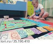 Ребенок играет в монополию в квартире на полу. Редакционное фото, фотограф Юлия Юриева / Фотобанк Лори