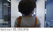 Mixed race businesswoman walking and drinking a cup of coffee in modern office. Стоковое видео, агентство Wavebreak Media / Фотобанк Лори