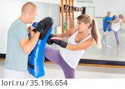 Concentrated young woman kicking boxing shield in gym. Стоковое фото, фотограф Яков Филимонов / Фотобанк Лори