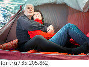 beautiful mature couple relaxing in a tent embracing each other on a summer day. Стоковое фото, фотограф Акиньшин Владимир / Фотобанк Лори