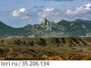 Loamy terrain with gullies and ravines without vegetation, and rocky mountains on the horizon (2020 год). Редакционное фото, фотограф Владимир Ушаров / Фотобанк Лори