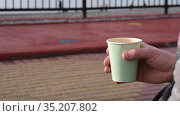 Man holds paper cup of coffee on contemporary city street. Стоковое видео, видеограф Ekaterina Demidova / Фотобанк Лори