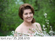 Portrait of middle-aged woman with bare shoulders near a cherry blossom. Стоковое фото, фотограф Володина Ольга / Фотобанк Лори