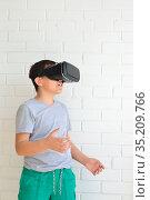 Boy with virtual reality glasses on brick wall background. Стоковое фото, фотограф Арестов Андрей Павлович / Фотобанк Лори