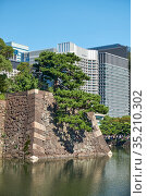 Old stone walls of Edo castle surrounded by moat with modern buildings on background. Tokyo. Japan (2019 год). Стоковое фото, фотограф Serg Zastavkin / Фотобанк Лори