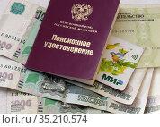 Пенсионное удостоверение с картой МИР лежит на российских купюрах. Редакционное фото, фотограф Елена Осетрова / Фотобанк Лори