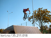 Male bmx biker jumps on ramp in skatepark. Стоковое фото, фотограф Tryapitsyn Sergiy / Фотобанк Лори
