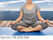 woman doing yoga in lotus pose over atlantic ocean. Стоковое фото, фотограф Syda Productions / Фотобанк Лори