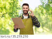male gardener with clipboard calling on smartphone. Стоковое фото, фотограф Syda Productions / Фотобанк Лори