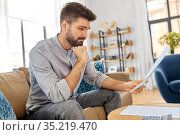 stressed man with bills at home. Стоковое фото, фотограф Syda Productions / Фотобанк Лори