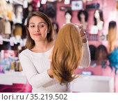 Cheerful young Latina selecting natural hair wigs in store. Стоковое фото, фотограф Татьяна Яцевич / Фотобанк Лори