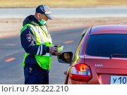 Russia Samara October 2020: traffic police officer check driver's documents on the highway. Russian text: DPS. Редакционное фото, фотограф Акиньшин Владимир / Фотобанк Лори
