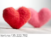 Two woolen handmade hearts stand on the white textured wooden boards. Стоковое фото, фотограф Георгий Дзюра / Фотобанк Лори