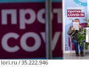 Мужчина читает анкету в очереди в мобильном пункте вакцинации от новой коронавирусной инфекции COVID-19 вакциной Спутник V в ГУМе города Москвы, Россия. Редакционное фото, фотограф Николай Винокуров / Фотобанк Лори