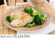 fried fillet of sea bass with garnish of broccoli on black warm stone plate. Стоковое фото, фотограф Татьяна Яцевич / Фотобанк Лори