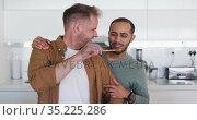Multi ethnic male same sex couple preparing food and tasting in kitchen. Стоковое видео, агентство Wavebreak Media / Фотобанк Лори