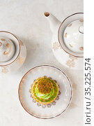 Pistachio cream cake and white tea set on the table, top view. Стоковое фото, фотограф Катерина Белякина / Фотобанк Лори