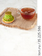 Shu cake with pistachio cream and tea on a linen napkin on the table, space for text. Стоковое фото, фотограф Катерина Белякина / Фотобанк Лори