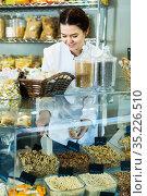 Young merchant is pouring on walnuts into bag. Стоковое фото, фотограф Яков Филимонов / Фотобанк Лори