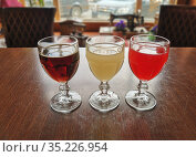 Traditional Russian soft drink kvass - bread, apple and cranberry. 3 glasses on a wooden table. Стоковое фото, фотограф Мария Сибатрова / Фотобанк Лори