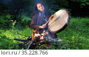 American Indian Shaman woman drumming in a trance at night in the forest by the fire. Стоковое видео, видеограф Алексей Кузнецов / Фотобанк Лори