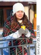 Woman drinking hot coffee from paper cup wrapping with red woollen scarf, wintertime, urban street. Стоковое фото, фотограф Кекяляйнен Андрей / Фотобанк Лори