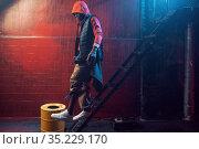 Stylish rapper in hoodie poses in grunge studio. Стоковое фото, фотограф Tryapitsyn Sergiy / Фотобанк Лори