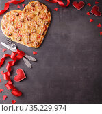 Valentine's Day. Romantic dinner. Heart shaped pizza, cutlery, red ribbon and hearts on a dark table. Стоковое фото, фотограф Сергей Молодиков / Фотобанк Лори