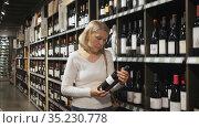 Positive middle aged blonde woman choosing bottled wine in modern wineshop. Стоковое видео, видеограф Яков Филимонов / Фотобанк Лори