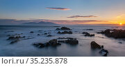 Rocks in Irish Sea at sunset, mountains in distance. St John's Point, Killough, County Down, Northern Ireland, UK. August 2020. Стоковое фото, фотограф Robert  Thompson / Nature Picture Library / Фотобанк Лори