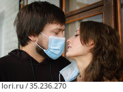 Young romantic loving couple wearing a protective face mask and staring at each other's eyes, St. Valentine's day during pandemic and quarantine. Стоковое фото, фотограф Ольга Балынская / Фотобанк Лори
